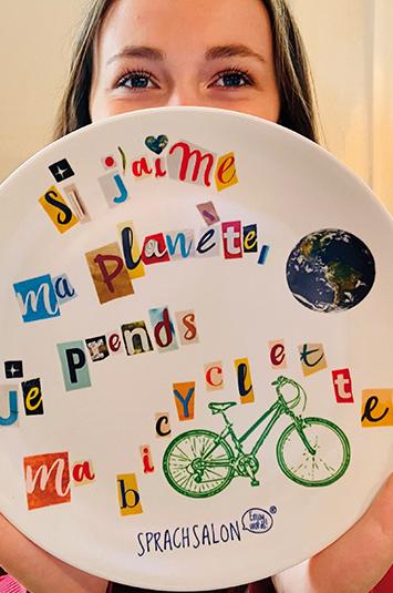Frau mit Teller auf dem ein Spruch zum Umweltschutz abgedruckt ist