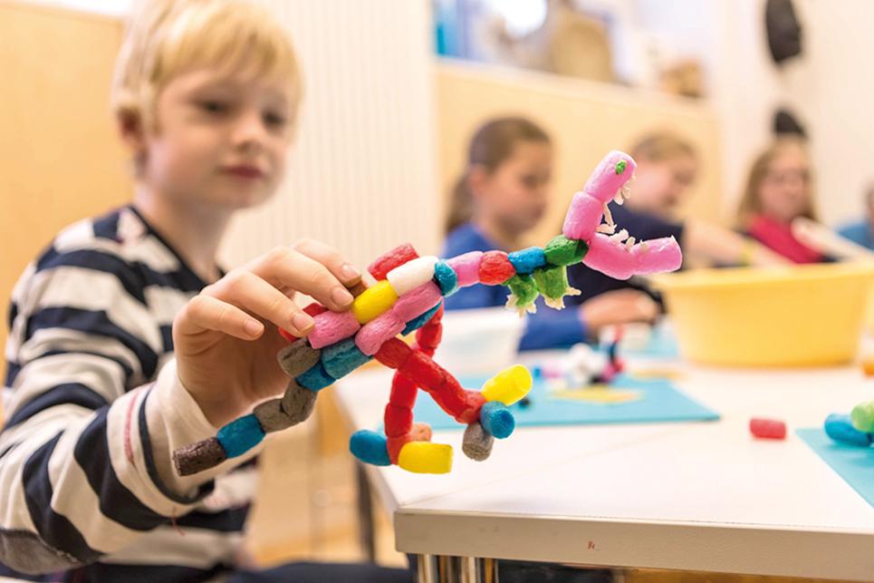 Junge mit einem aus PlayMais hergestellten Dinosaurier-Modell