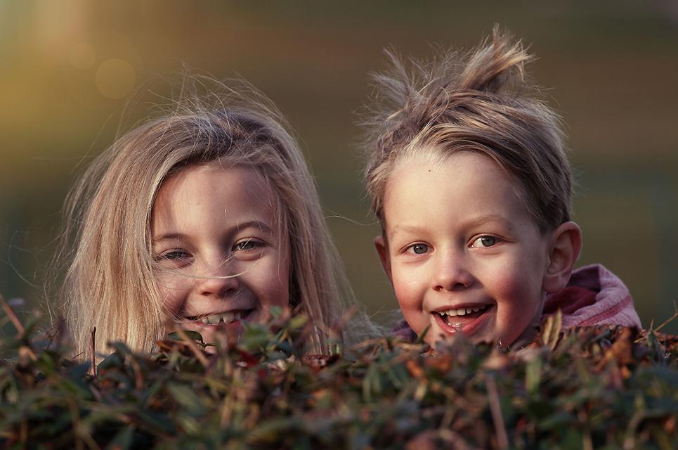 Ein Mädchen und ein Junge lugen hinter einer Hecke hervor
