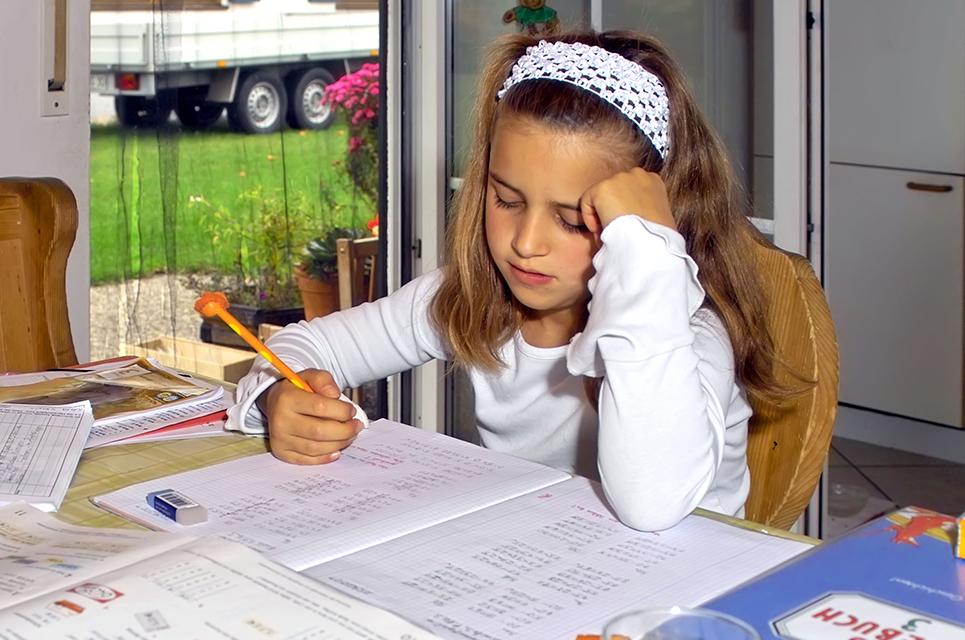 Mädchen sitzt genervt am Küchentisch an ihren Hausaufgaben
