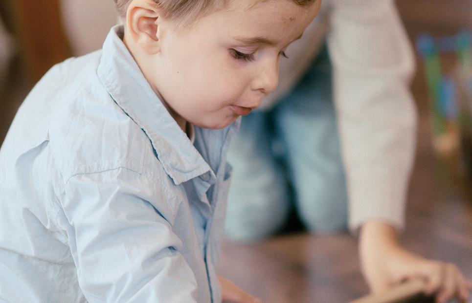 Kind spielt mit Holzeisenbahn