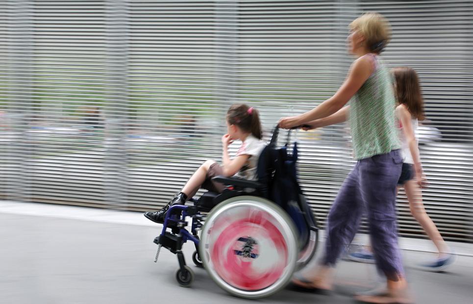 Eine Mutter schiebt ihr Kind im Rollstuhl.
