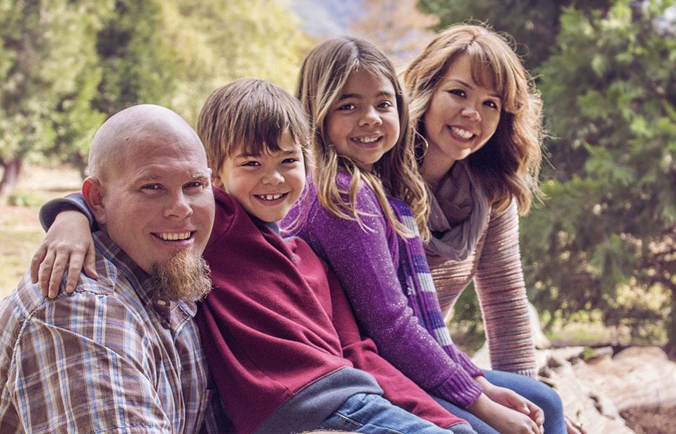 Familie sitzt auf Baumstamm