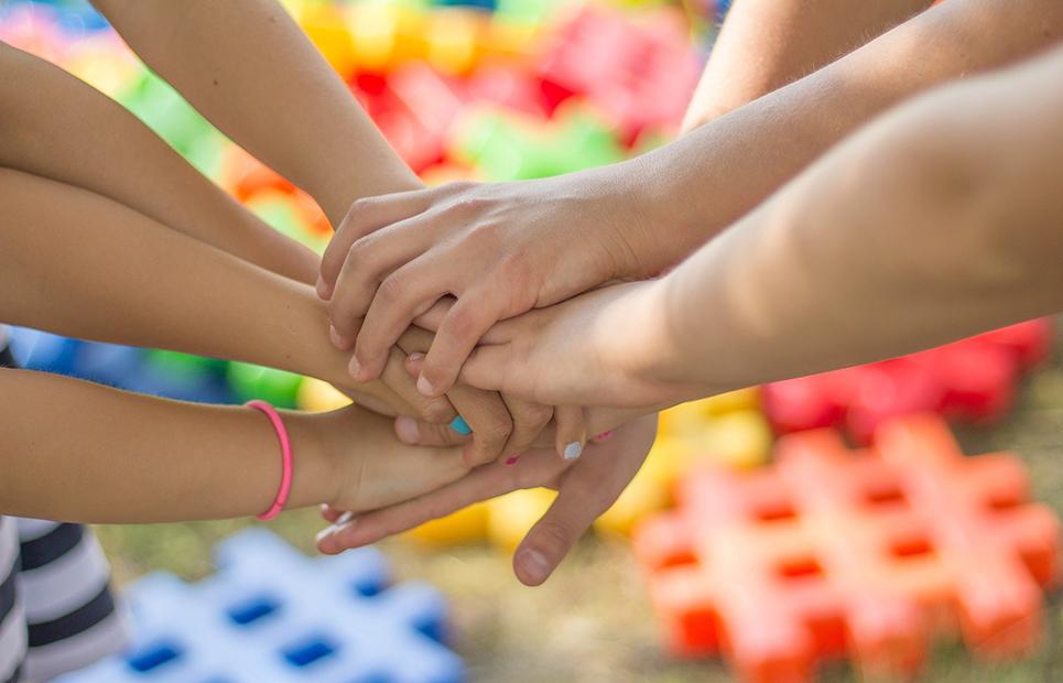 Viele Kinderhände liegen übereinander