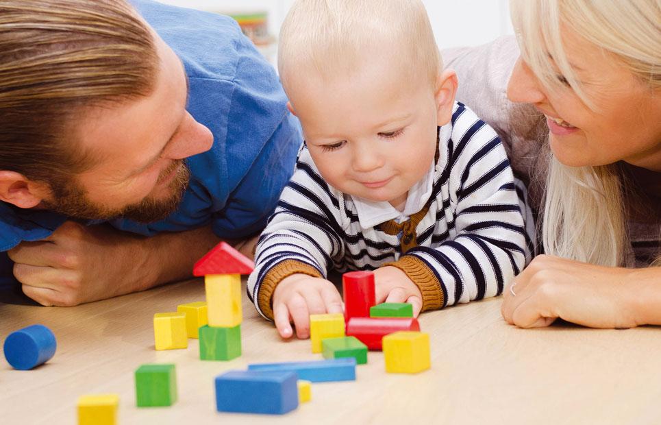 Eltern und Kind spielen Bauklötze