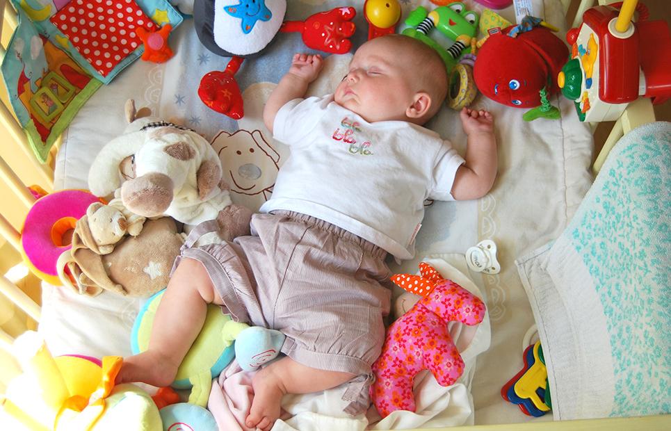 Schlafendes Baby umgeben von Spielzeug