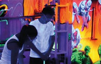 Ein Mann und eine Frau spielen im Schwarzlicht Minigolf