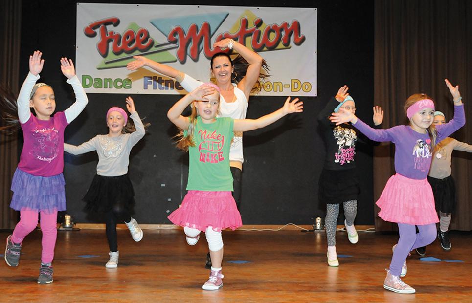 Tanzende Mädchen mit einer Trainerin auf einer Bühne