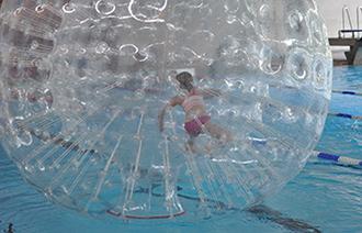 Kind in einem Wasserlaufball im Schwimmbecken des TaunaBades