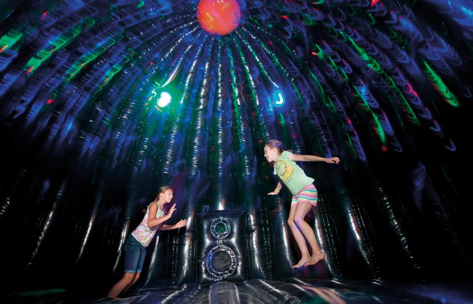 Kinder hüpfen in einer Discohüpfburg mit Licht und Musikanlage