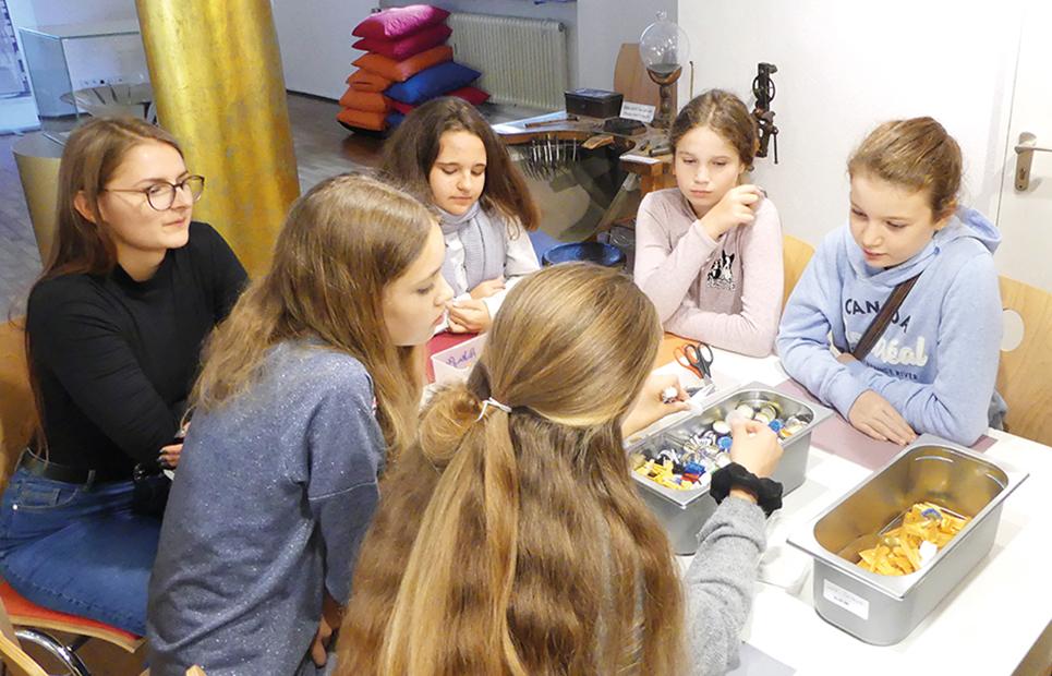 Mädchen sitzen an deinem Tisch bei einem Workshop