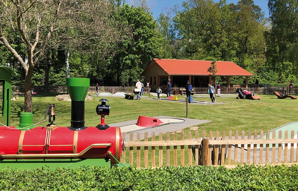 Blick auf eine Minigolfanlage, im Vordergrund die Park-Eisenbahn der Lochmühle