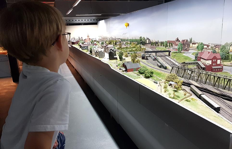 Junge schaut auf eine Anlage einer Modelleisenbahn