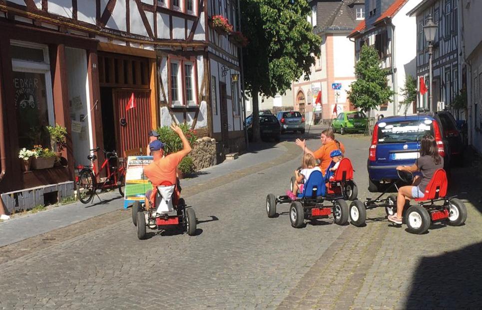 Mehrere Tretauto-Fahrer sind in einer Straße unterwegs