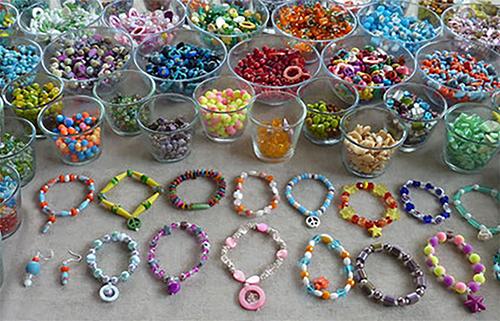 Perlenbänder und Schalen mit vielen verschiedenen bunten Perlen