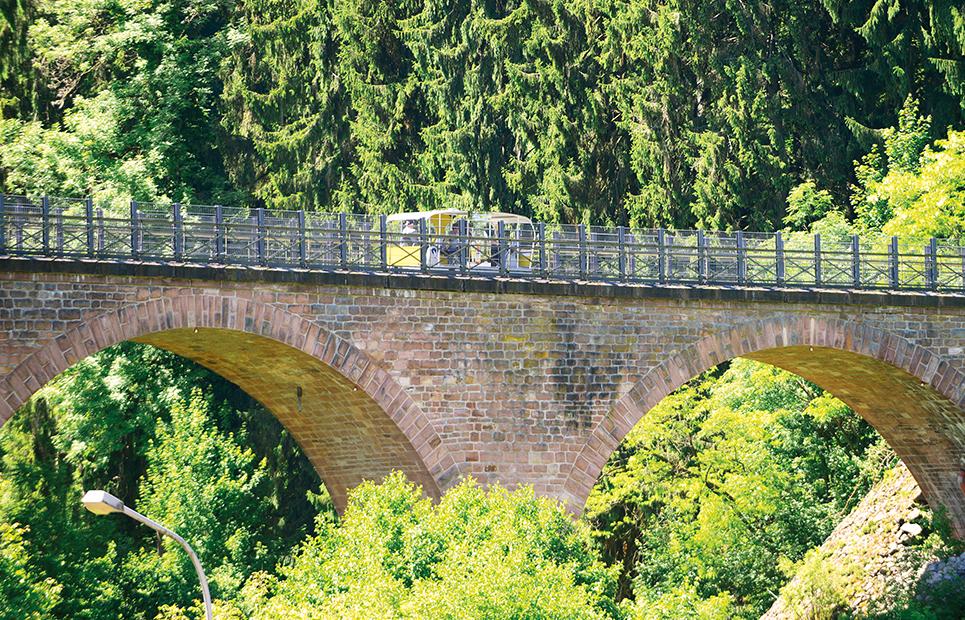 Blick auf eine Solardraisine die über eine Brücke fährt