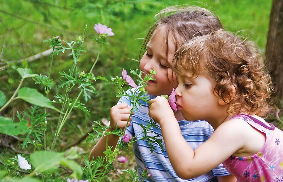 Zwei Mädchen die an Blumen schnuppern