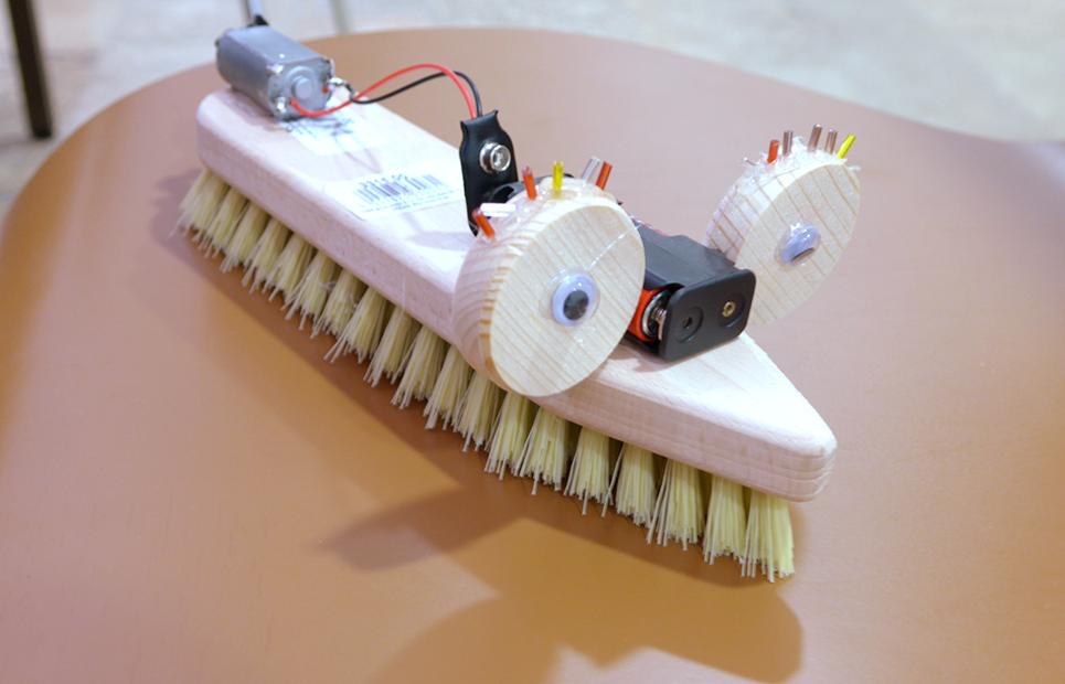 Eine Bürste, die mit einem Elektromotor und Batterien ausgestattet ist und mit Augen beklebt wurde